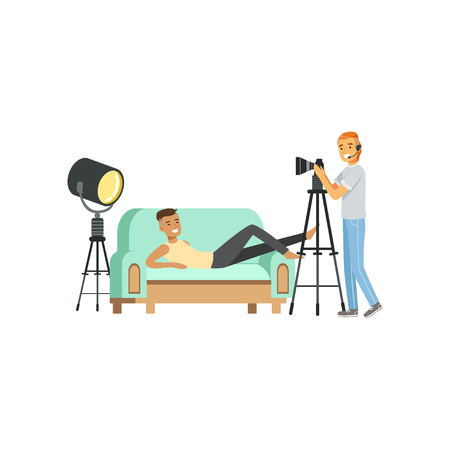 Cartoon guy model character posing lying on couch. Photographer with headphone and professional camera on tripod. Shooting process in studio. Flat vector 向量圖像