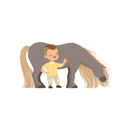 Little boy standing next to a pony