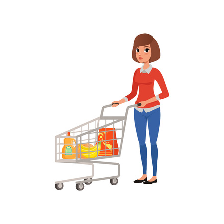 Cartoon woman standing near supermarket cart with products. Shopping in grocery store. Young girl in blouse and jeans. Flat vector design