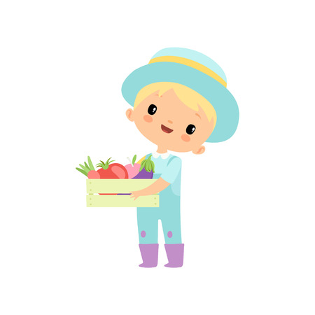 Garçon mignon en salopette, bottes en caoutchouc et chapeau tenant une boîte en bois pleine de légumes, personnage de dessin animé de jeune agriculteur engagé dans des activités agricoles Illustration vectorielle sur fond blanc.