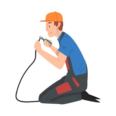 Male Electrician Engineer Sitting on His Knee Repairing Cable with Pliers, Electricity Maintenance Service Worker Character in Uniform and Cap Cartoon Style Vector Illustration Isolated on White Background.