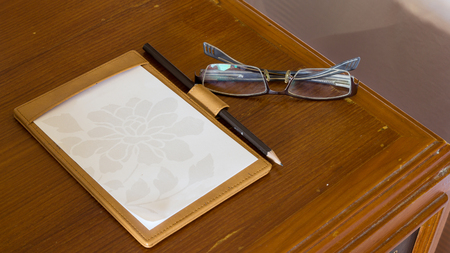 background, texture of notebook paper with pencil and spectacles on wood table photo