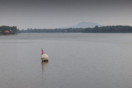 the buoy with red flag on water of sea, river photo