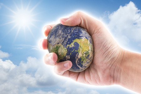 hand is holding to the stone world on blue sky background photo