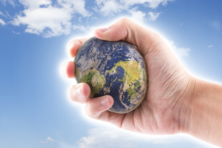 hand is holding to the stone world on blue sky background, the world map by nasa photo