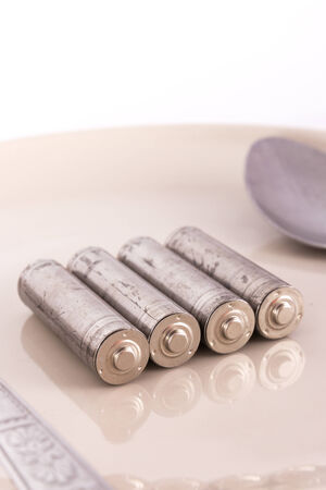 the isolated of old AA battery in food dish is energy consumption concept photo