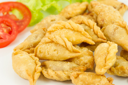 Khanom Pun Klib or Small Curry Stuffed Puff is small pir consisting of specialised curry with chicken and potatoes in deep-fried or baked pastry shell. Stock Photo