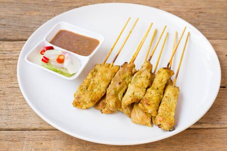 satay sauce: Pork satay with peanut sauce and cucumber slices and onions in vinegar Stock Photo