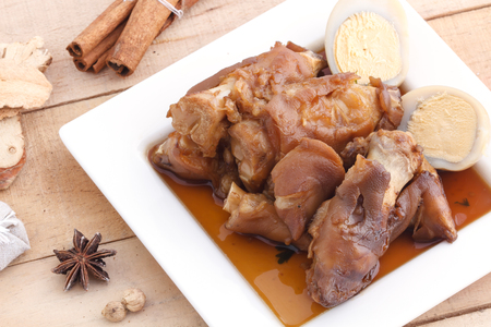 stewed: Stewed pork leg in white dish on wood background. Stock Photo