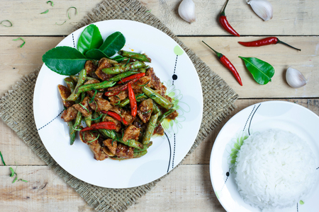 string top: Stir fried pork and red curry paste with string bean on wood background,Top view