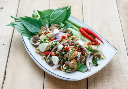 spicy cockle salad on wooden background, selection focus
