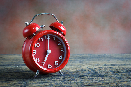 Red double bell alarm clock and book on wooden background Stock Photo