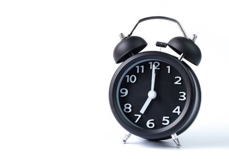 seven o'clock: Black double bell alarm clock showing seven oclock on white background