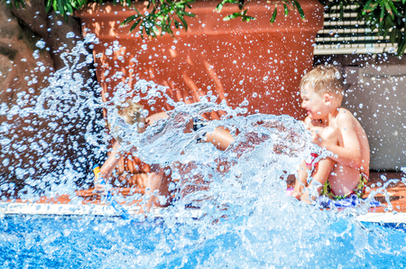 Splash water in the pool against the background of playing children