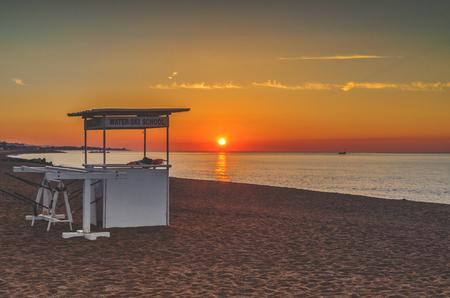 Coast in Spain Costa Brava, gazebo for surfers at sunset