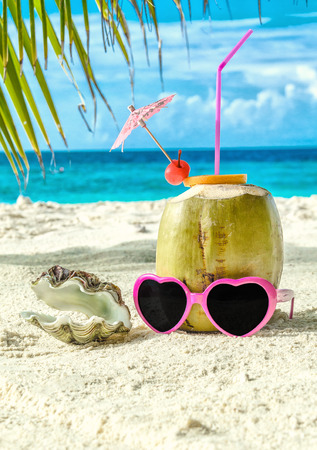 Coconut, pink sunglasses and seashell on sand close-up