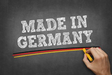 hand writing MADE IN GERMANY on chalkboard - underlining with colors of german flag