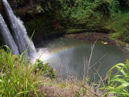 kauai: A waterfall produces a rainbow on Kauai