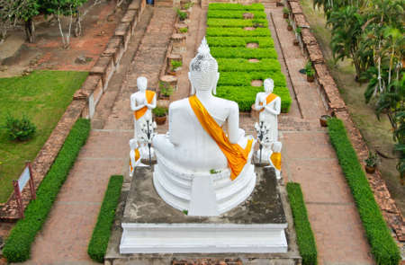 The white buddha statue in ruined old temple at Wat Yai Chai Mongkol temple, Ayutthaya, Thailand photo