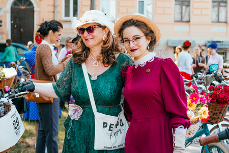 Kiev, Ukraine - May 12, 2018: Two ladies in vintage dresses participating in bicycle tweed run Retro cruise on May 12, 2018 in Kiev, Ukraine.
