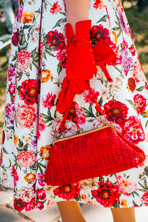 Kiev, Ukraine - May 12, 2018: Detail of outfit girl in floral print dress, red gloves and bag participating in bicycle tweed run Retro cruise on May 12, 2018 in Kiev, Ukraine.