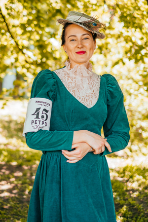 Kiev, Ukraine - May 12, 2018: Girl in teal color vintage dress with lace details, straw hat with peacock feather participating in bicycle tweed run Retro cruise on May 12, 2018 in Kiev, Ukraine.