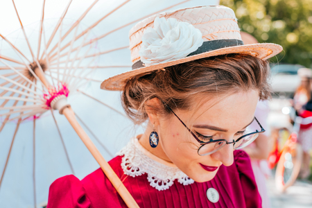Kiev, Ukraine - May 12, 2018: Girl in vine red vintage dress and glasses with japanese umbrella participating in bicycle tweed run Retro cruise on May 12, 2018 in Kiev, Ukraine.