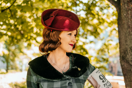Kiev, Ukraine - May 12, 2018: Girl in checked vintage dress, fascinator hat and red lipstic participating in bicycle tweed run Retro cruise on May 12, 2018 in Kiev, Ukraine. Editorial