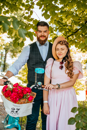Kiev, Ukraine - May 12, 2018: Couple in vintage clothes participating in bicycle tweed run Retro cruise on May 12, 2018 in Kiev, Ukraine.