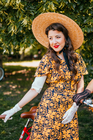Kiev, Ukraine - May 12, 2018: Girl in floral print dress, straw hat, gloves and red lipstick participating in bicycle tweed run Retro cruise on May 12, 2018 in Kiev, Ukraine.