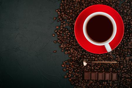 Weiße Tasse Kaffee auf dem roten Teller mit gerösteten Kaffeebohnen, Goldlöffel und Milchschokolade auf dem schwarzen Betonsteinhintergrund. Flatlay-Stil.