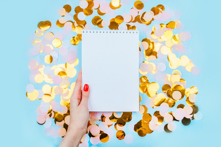 Woman holding clean note pad on the gold confetti and pastel blue background. Festive design.
