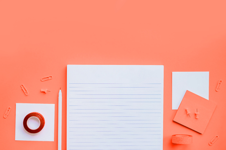 Beautiful office stationery flatlay with ruled notebook, white pen, sticky notes and paper clip on the bright desk with pink background.