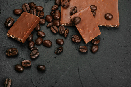 Roasted coffee beans and bars of milk chocolate on the black concrete stone background. Flatlay style. 免版税图像