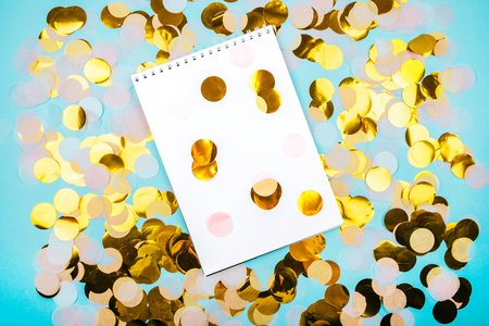Clean note pad on the gold confetti and pastel blue background. Festive design.