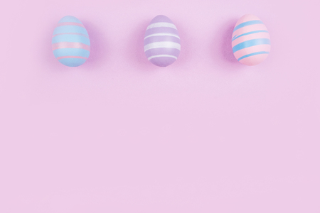 Three dyed on blue, pink and violet Easter eggs isolated on purple background. Easter theme flatlay.