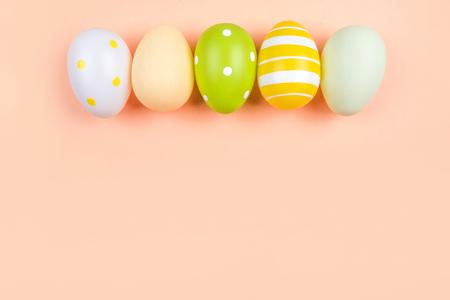 La rangée d'oeufs de Pâques teints sur vert, jaune et gris isolé sur fond de pêche. Flatlay thème de Pâques. Banque d'images
