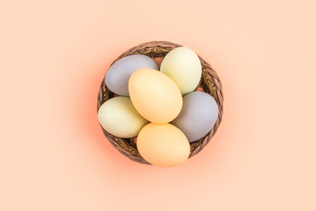 Flatlay with dyed on green, yellow and grey Easter eggs in the straw basket isolated on peach background. Easter theme flatlay. Imagens