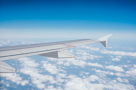 Wing of the airplane with the view of beautiful blue sky and clouds. Reklamní fotografie