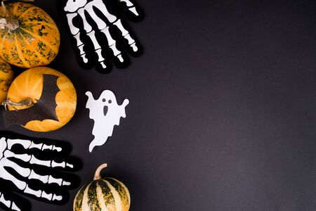 Top view of Halloween pumpkins, autumn leaves, paper craft bats, ghost, and skeleton on black background.