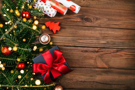 Christmas flatlay with black box and red ribbon decoration, fir tree branches, wrapping paper, tree decoration, gold bells and bokeh lightening on rustic brown wooden background. Stock Photo