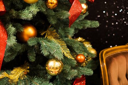 Christmas tree decoration and garland with golden bokeh lightening background.