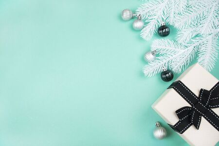 Christmas flatlay with beige gift box, silver baubles and white pine tree branches isolated on mint green background. New Year concept.