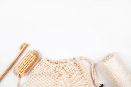 Flatlay with bamboo toothbrush, konjac and loofahs sponges, wooden brush and cotton mesh produce bag isolated on white background. Zero waste concept.