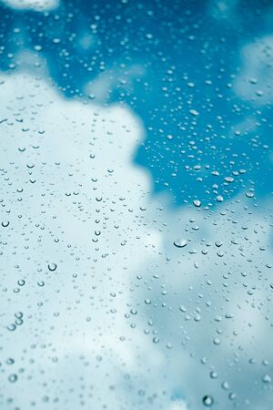 Rain drops on window pane glass surface with cloudy background.