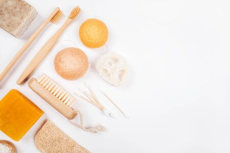 Flatlay with wooden brush, bamboo toothbrushes, bar of soap, konjac and loofahs sponge and cotton earbuds isolated on white background. Zero waste concept.
