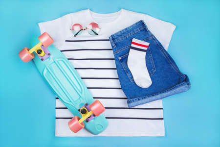 Sport inspired flatlay with turquoise penny skateboard, white striped t-shirt, socks, denim shorts and round grasient sunglasses isolated on blue background.