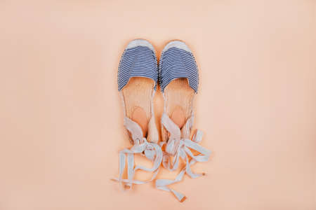 Summer fashion flatlay with striped espadrilles sandals isolated on beige background.