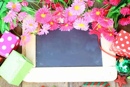 Beautiful flowers and gift box over chalk board