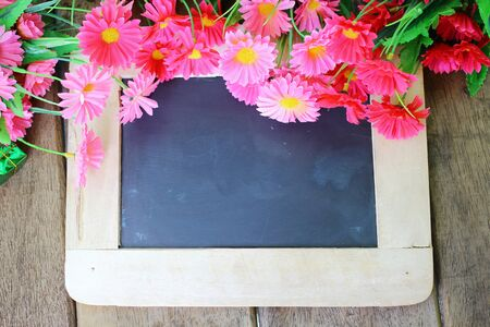 Beautiful flowers and chalk board on wooden background